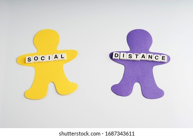 Social distance concept via text on top of human shape from paper. Keep the distance between person to avoid transmitting the COVID-19 virus.