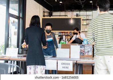 Un serveur conceptuel de la distance sociale de petite entreprise au service du client au café.