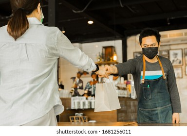 Social distance conceptual waiter giving food client at small business food.