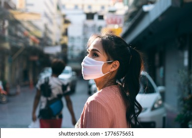 Social distance and new normal lifestyle virus protect at outdoor area concept. Asian adult woman tan skin wear mask on face. Background chinatown landmark destination. Bangkok, Thailand.