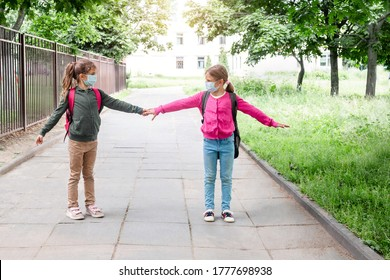 Social distance in school concept. Schoolchildren in protective masks show social distance of 6 feet. Back to school during coronavirus pandemic. School child wearing protective face mask in school.