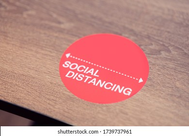 Social Distance word sticker on the table in restaurant.Social Distancing Instruction against the Spread.New normal Reopen Mall, School.Social distancing in the workplace during coronavirus COVID-19.