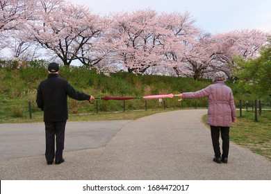 Social distancing (6 feet / 2 meters) to avoid the spread of coronavirus (COVID-19). Two people stand apart holding two umbrellas. A new concept along with elbow bumping. New normal.