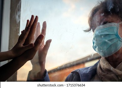 social distancing among the family, hand of the woman and her grandchildren on window plane, concept coronavirus and covid-19 pandemic