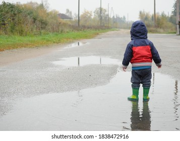 Social distancing- autumn and rainy day. Little kid with rubber boots in the puddle.