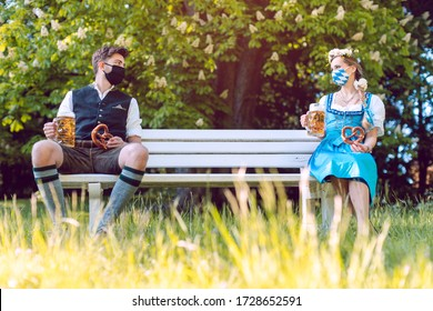 Social distancing in Bavaria at the beer garden, man and woman sitting apart