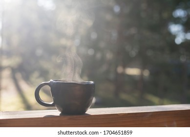 Social distancing and beautiful morning mood on terrace of log house in forest with closeup of unique handmade coffee mug of black pottery.