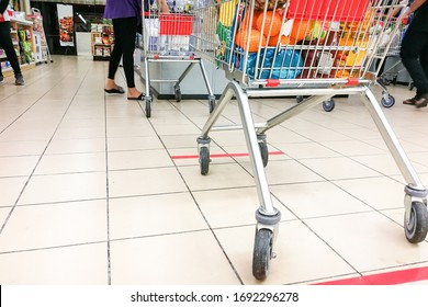 Social distancing being practiced at supermarket payment counter in Malaysia, with 1 meter gap between people in queue.