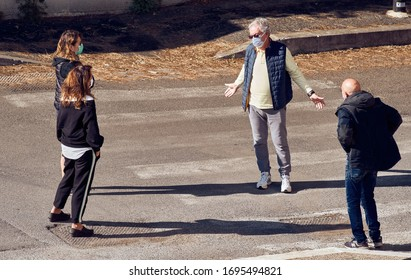 Social Distancing, Coronavirus Lockdown: Hugging at Risk of Infection for Worried Old Man and Young Women (All Wearing Face Masks) Gathering in the Street in Covid-19 Quarantine. Symbolic. April 2020