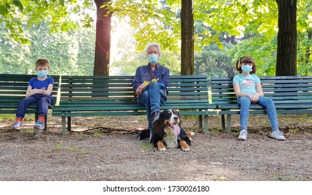 social distancing: grandfather and grandchildren are sitting on park benches with masks during the coronavirus pandemic