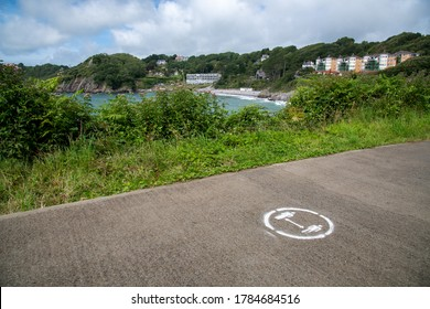 Social distancing painted sign on the floor at Caswell Bay Beach coastline path in Gower, Swansea Wales