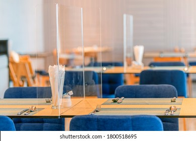 Social distancing at Restaurant. Seat for customers sitting separated in restaurant with table shield plastic partition to protect infection from coronavirus covid-19