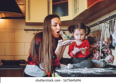 Social Distancing and Self-Isolation, stay home, quarantine, families self-isolating together for Novel Coronavirus COVID-19. Mom and toddler daughter play in the kitchen