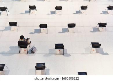 La distanciation sociale, Un homme s'assoit, discute sur un smartphone, attend dans des rangées de chaises vides éloignées les unes des autres pour ralentir la propagation du virus, la transmission de la maladie, réduire les contacts et l'infection pendant la pandémie de Covid-19