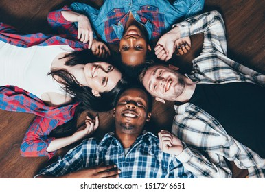 Social diversity. International friendship unity. Group of happy interracial people lying in circle.