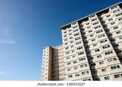 Social housing apartment tower block against a blue sky.