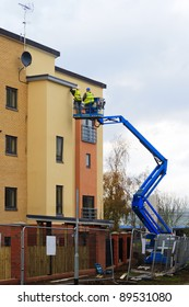 Social housing development with cherry picker and workers