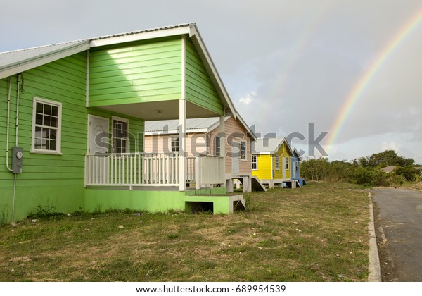 Social Housing with a double Rainbow. The government takes on the responsibility of providing affordable housing for the citizens of Barbados creating estates of low cost houses in bright colours.