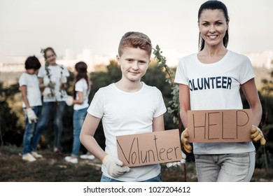 Social initiative. Joyful positive nice woman holding a volunteer sign and smiling while standing near the boy