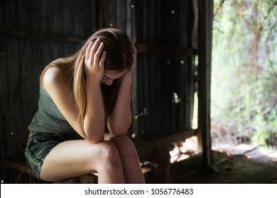 Social issue of Stress, depress, headache, addiction concept. Young Asian woman hands touching her head in abandoned house at rural forest.