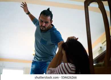 Social issues, abuse and aggression on women, young drunk man hitting and beating woman at home after drinking alcohol. Violent husband fighting with abused wife
