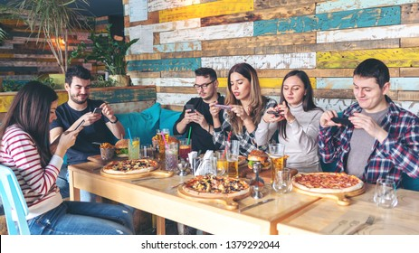 Social media addiction concept with young people photographing food in rustic restaurant – happy friends taking picture of pizza and hamburgers with mobile phones to post online, connected millennials