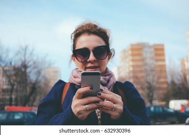 social media addiction - smartphone in woman's hands texting while  walking on the street not being careful