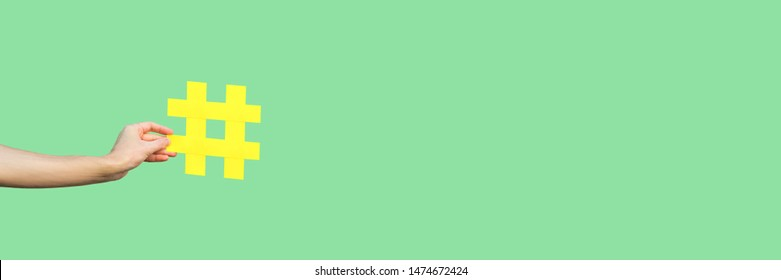 Social media concept. closeup of human hand holding and showing large big yellow hashtag sign. indoor studio shot, isolated on light green background copyspace. marketing symbol, instagram followers.
