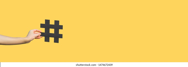Social media concept. closeup of human hand holding and showing large big black hashtag sign. indoor studio shot, isolated on yellow background copyspace. marketing symbol, instagram followers.