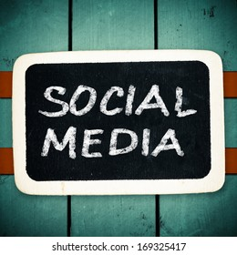 Social media concept - text on a blackboard on wood backround