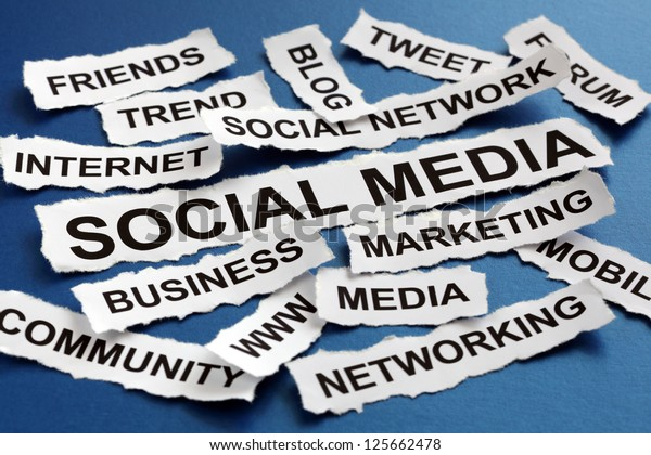 Social media concept torn newspaper headlines reading marketing, networking, community, internet etc