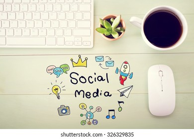 Social Media concept with workstation on a light green wooden desk