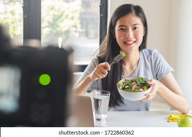Social media and content creator occupation new job in future. beauty asian blogger eating fresh homemade salad breakfast and recording video for online channel live.