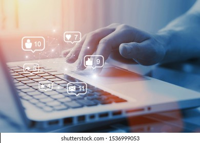 Social media and digital marketing concept. SMM using in business. Closeup view of hand touching laptop with icons like, share, email, message etc. with copyspace on background.