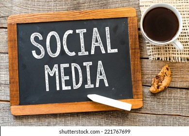 Social Media handwritten with white chalk on a blackboard, cup of coffee and biscuit on a wooden background