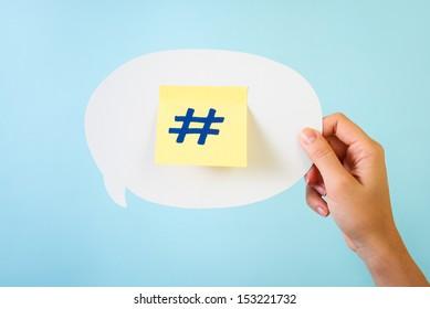Social media hashtag symbol / sign written on stick-note over white speech bubble ballon, blue background. Hand holding speech bubble message.