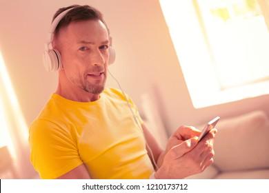 Social media. High-spirited joyful man checking social media while listening to the music