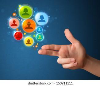 Social media icons coming out of gun shaped hand, social media concept