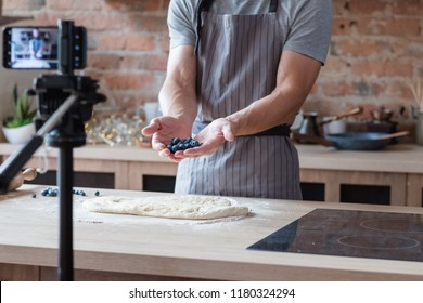 social media influencer or food blogger creating content. man shooting a cooking video using camera on tripod. chef holding bluberries in hands and showing them to viewer.