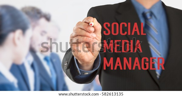 Social Media Manager, Male hand in business wear holding a thick pen writing, with office team blurred in background, digital composing.