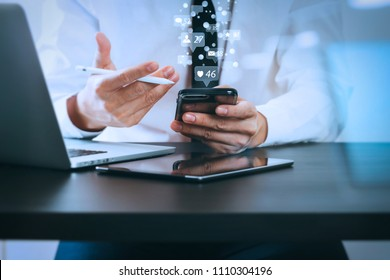 Social media and Marketing virtual icons screen concept.close up of businessman working with smart phone on wooden desk in modern office with virtual icon diagram with glass reflected view