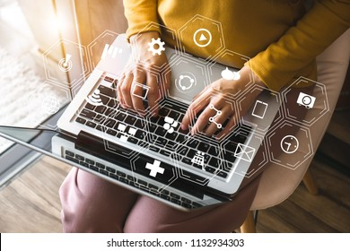 Social media and Marketing virtual icons screen concept.close up of businessman typing keyboard with laptop computer on wooden desk in modern office