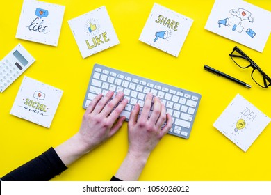 Social media promotion. Work desk with socail media icons. Yellow background top view. Hand is typing