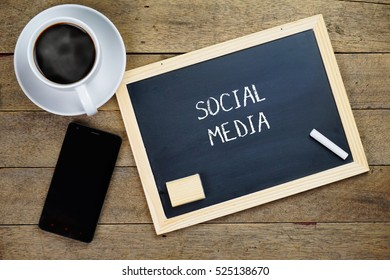 SOCIAL MEDIA text written on chalkboard. Chalkboard, smartphone and a cup of coffee on the wooden background.