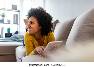 Social media time. Staying in touch with her tablet. Cheerful woman sitting on couch using tablet pc at home in the living room. Smiling young woman with tablet on the sofa