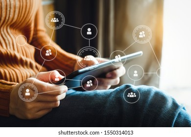 Social network theme hologram with businessman working on computer laptop, smartphone, and tablet with VR icons on background.