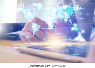 Social networking technology conceptual with businessman using computer tablet and finger touching screen with orange light and show blue world map with people icon symbol connecting the world