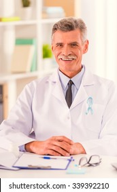 The social problem of male diseases. Portrait of doctor with blue ribbon sitting in his office