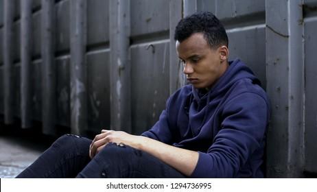 Social problems, african-american homeless boy feeling loneliness, hopeless guy
