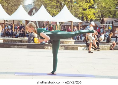 Social project of popularizing yoga on the streets of cities. A young sporty beautiful woman is practicing yoga asana tuladandasana against the background of a crowd of people.